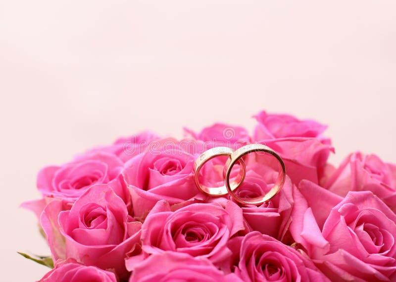 Grupo de alianças de casamento na rosa do rosa tomada fotos de stock