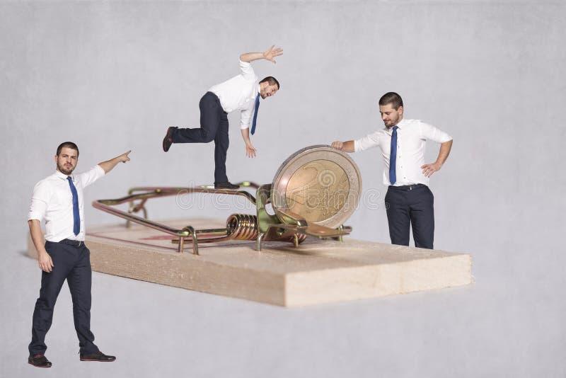 Grupo de alimentações dos homens de negócios em seu dinheiro fotografia de stock