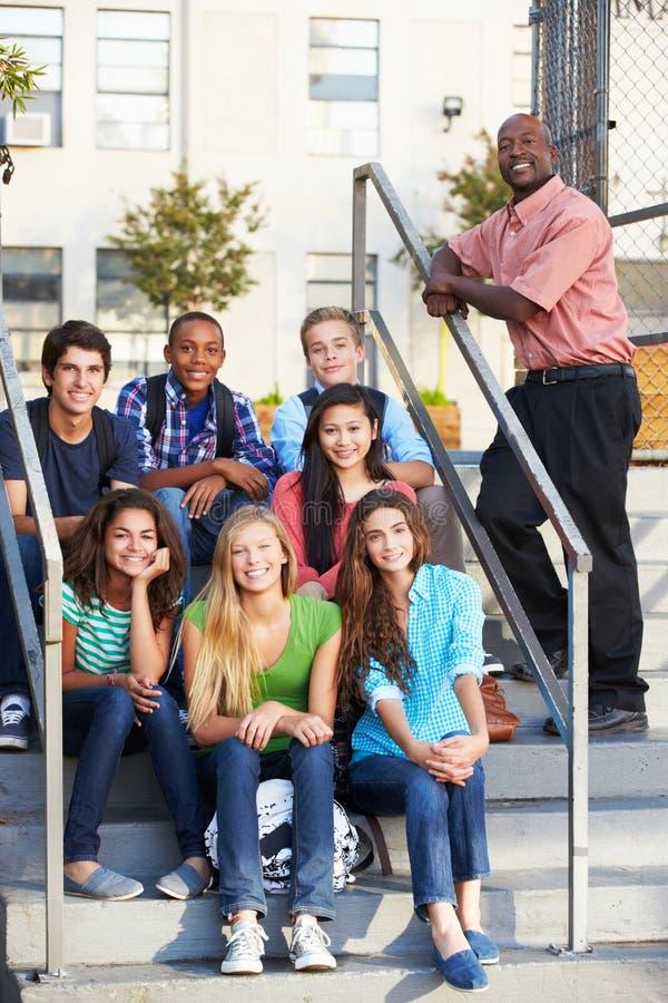 Grupo de alumnos adolescentes fuera de la sala de clase con el profesor fotos de archivo libres de regalías