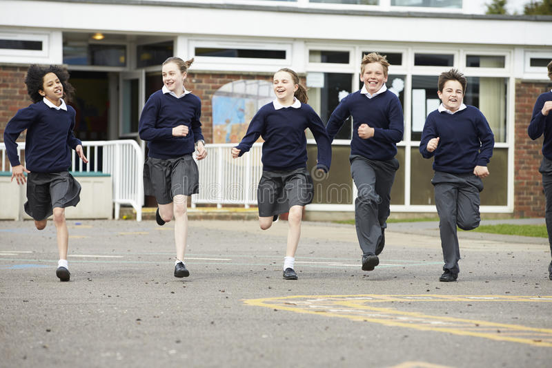 Grupo de alumnos de la escuela primaria que corren en patio foto de archivo