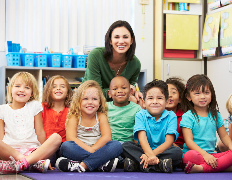 Grupo de alumnos elementales en sala de clase con el profesor imágenes de archivo libres de regalías
