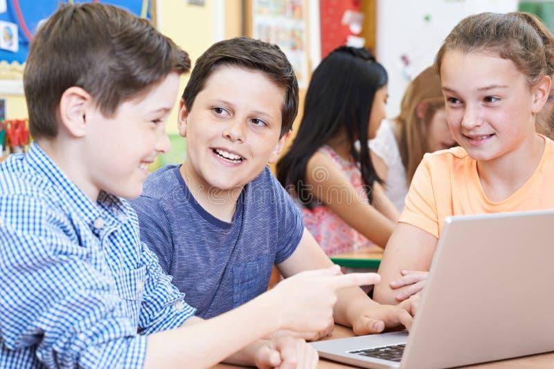 Grupo de alumnos elementales que trabajan junto en ordenador imagenes de archivo