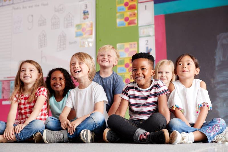 Grupo de alumnos de la escuela primaria que se sientan en piso en sala de clase imagen de archivo libre de regalías