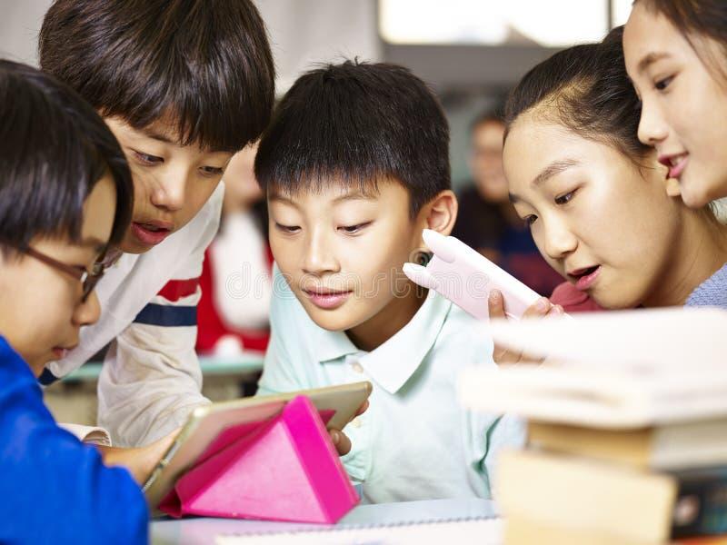 Grupo de aluno asiático da escola primária que joga o jogo usando a tabuleta imagens de stock royalty free