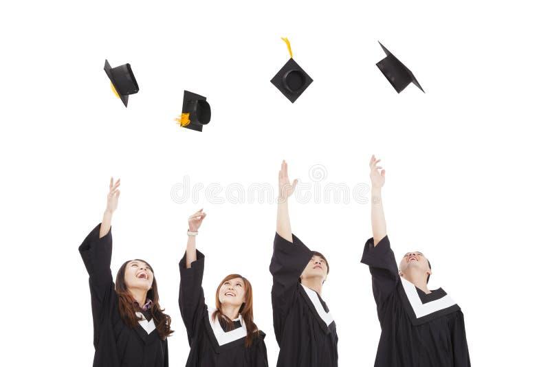 Grupo de alunos diplomados que joga o chapéu imagens de stock royalty free