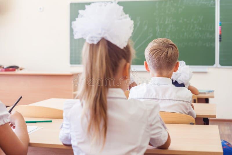 Grupo de alunos na sala de aula da escola que senta-se na mesa foto de stock