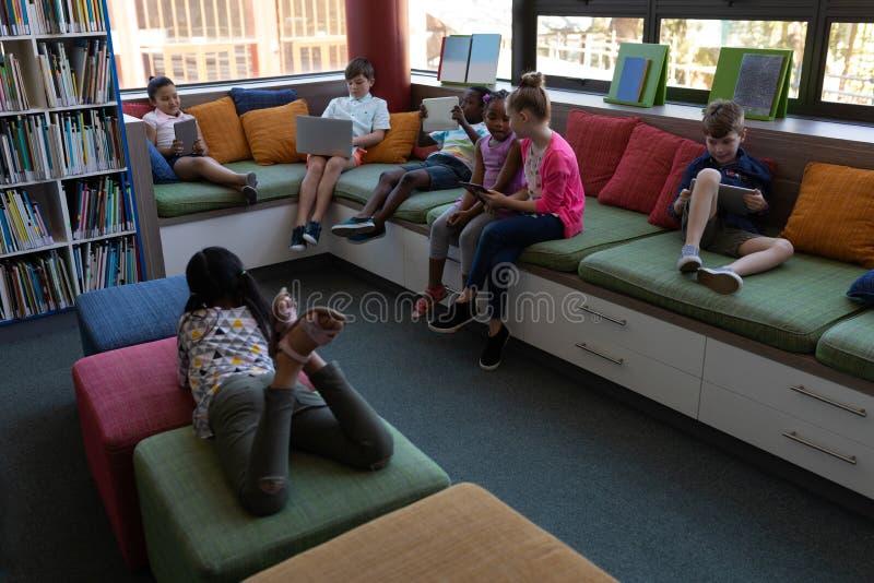 Grupo de alunos que estuda ao sentar-se no sofá na biblioteca escolar fotos de stock royalty free