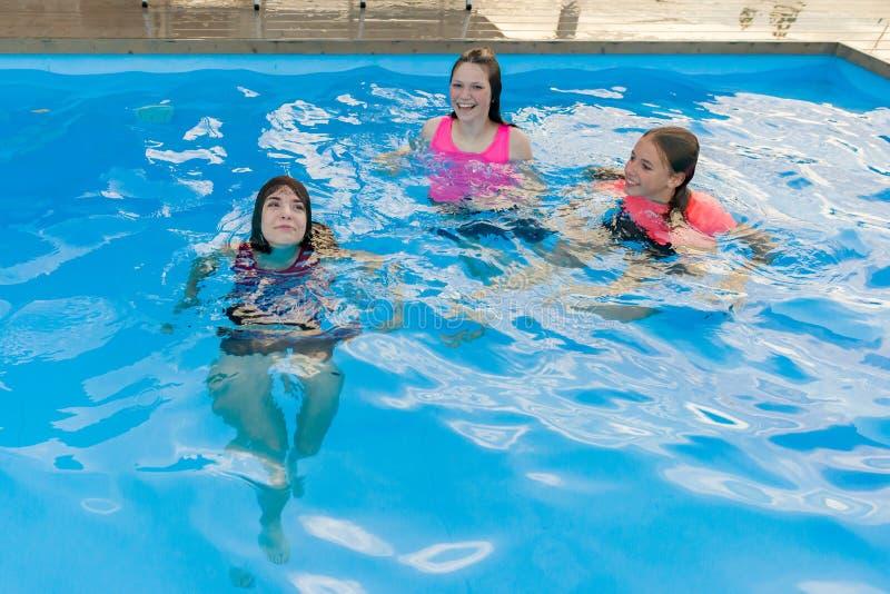 Grupo de 3 amigas adolescentes que têm o divertimento na piscina imagens de stock