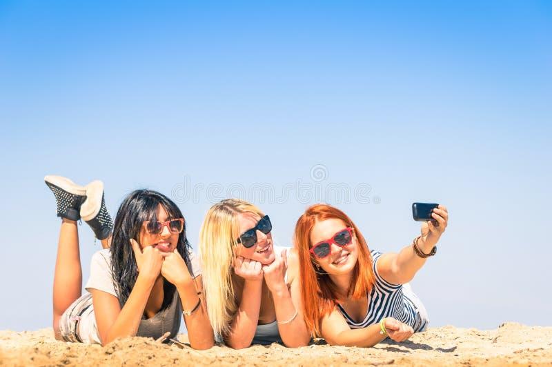 Grupo de amigas novas felizes que tomam um selfie na praia fotos de stock