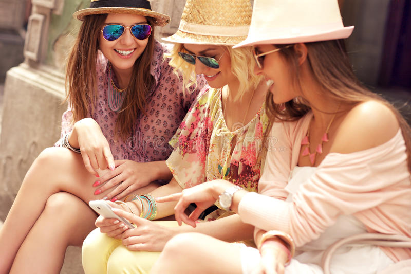 Grupo de amigas que usan smartphones imagenes de archivo