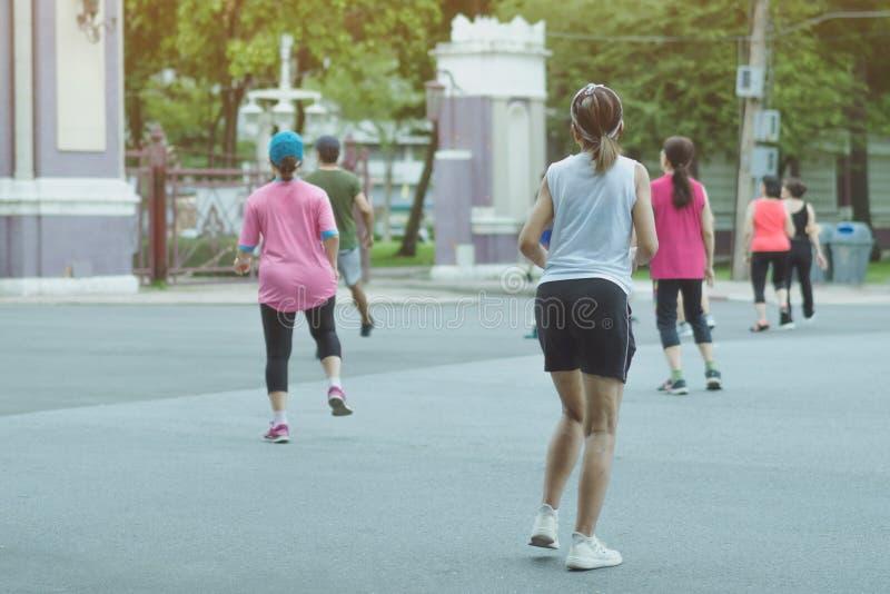 Grupo de amigo mayor que hace danza aerobia después de trabajo junto en el parque de Lumpini fotos de archivo