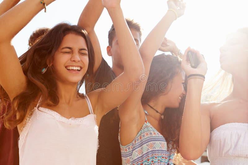 Grupo de amigos adolescentes que dançam fora contra Sun imagem de stock