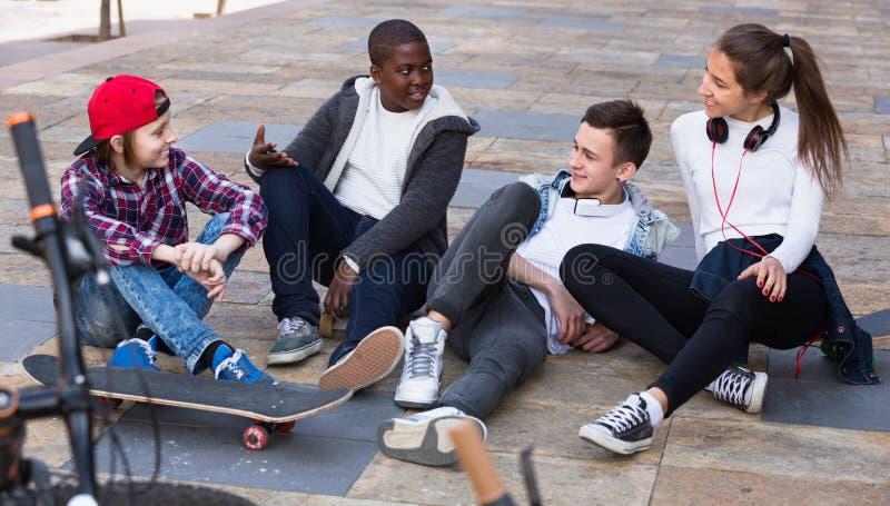 Grupo de amigos adolescentes que se relajan y que charlan foto de archivo