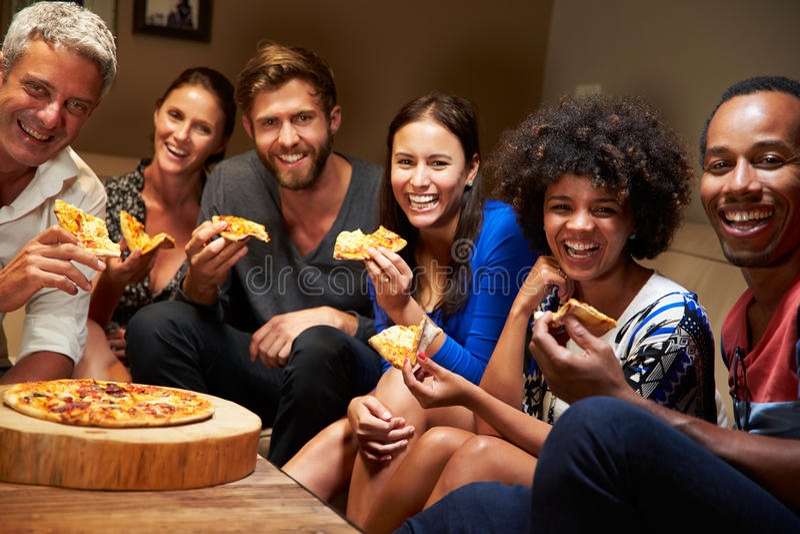 Grupo de amigos adultos que comem a pizza em uma festa em casa foto de stock