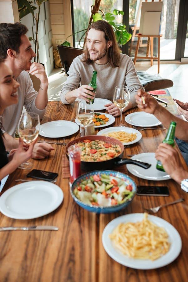 Grupo de amigos alegres que comen y que hablan en la tabla imagen de archivo libre de regalías