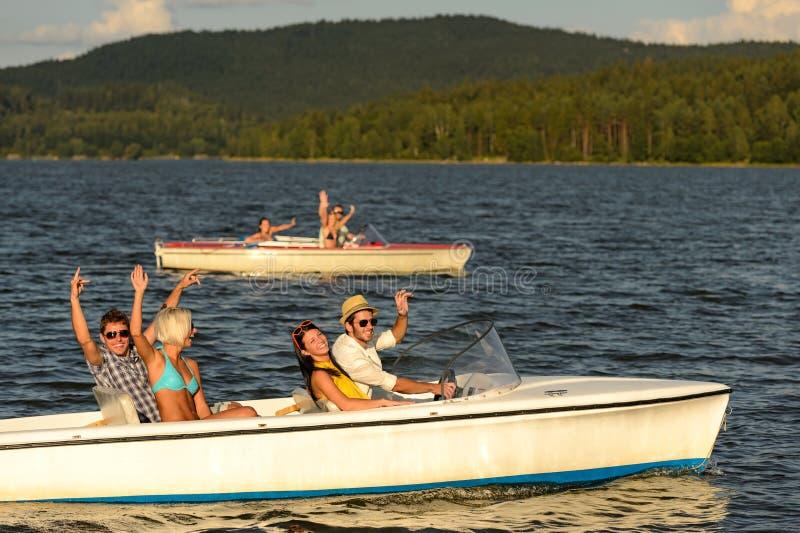 Grupo de amigos que competem com motorboats fotos de stock