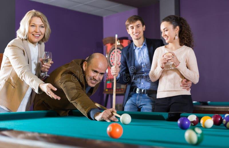 Grupo de amigos alegres que juegan billares y la sonrisa imagen de archivo libre de regalías