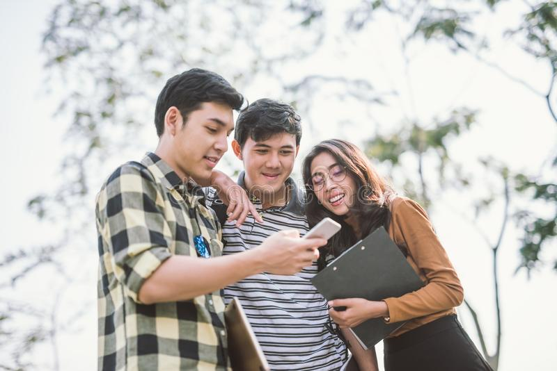 Grupo de amigos alegres que miran el teléfono elegante al aire libre fotografía de archivo libre de regalías