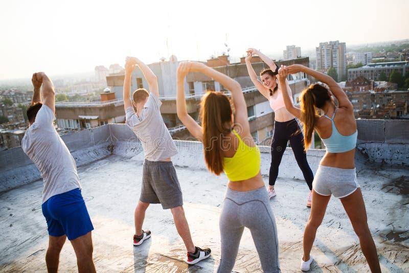 Grupo de amigos aptos felizes dos jovens no sportswear que faz exerc?cios Esporte fora imagem de stock royalty free