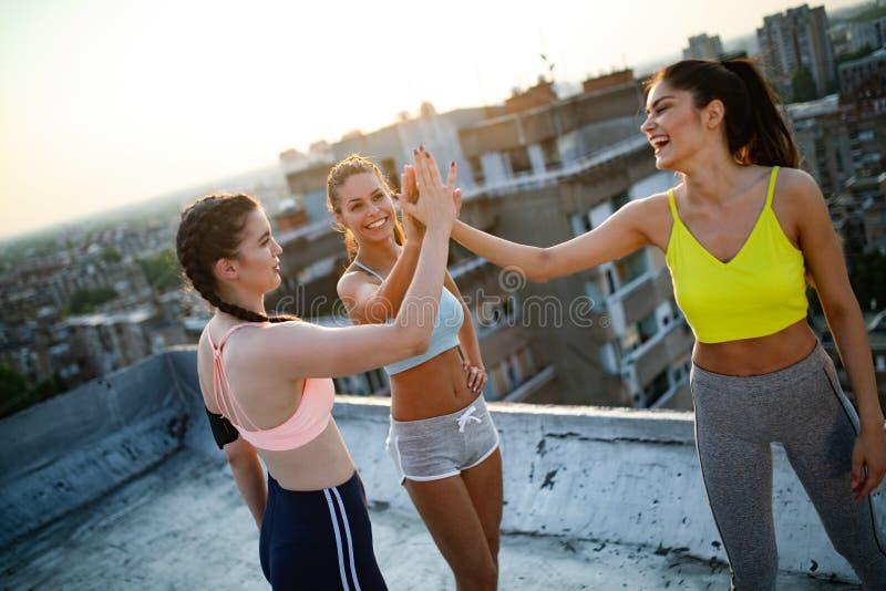 Grupo de amigos aptos felizes dos jovens no sportswear que faz exerc?cios Esporte fora imagem de stock