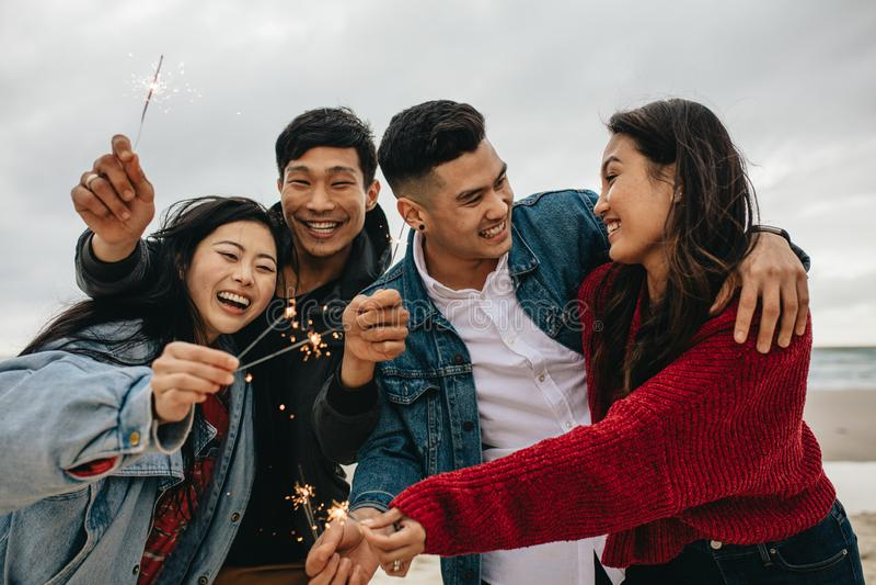 Grupo de amigos asiáticos que comemoram a praia ay do dia de ano novo imagem de stock royalty free