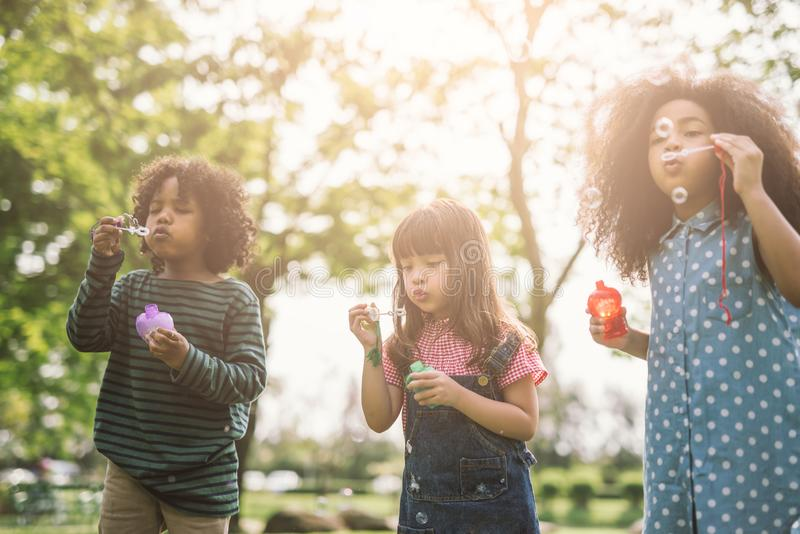 Grupo de amigos bonitos das crianças diversas que têm o divertimento da bolha no gramado verde no parque imagens de stock royalty free