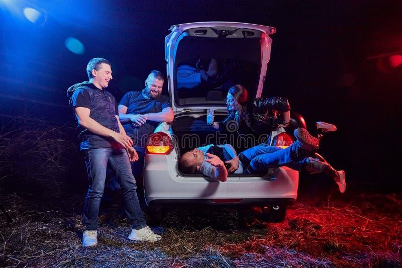 Grupo de amigos cerca del coche en la noche y un individuo borracho que mienten en el tronco Photoshoot sobre la vida de gungster imagen de archivo