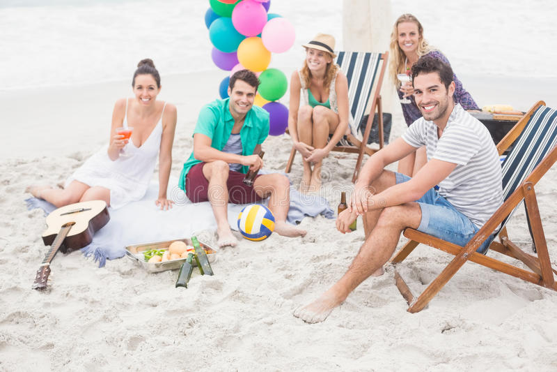 Grupo de amigos com as bebidas que têm o divertimento junto na praia fotos de stock royalty free