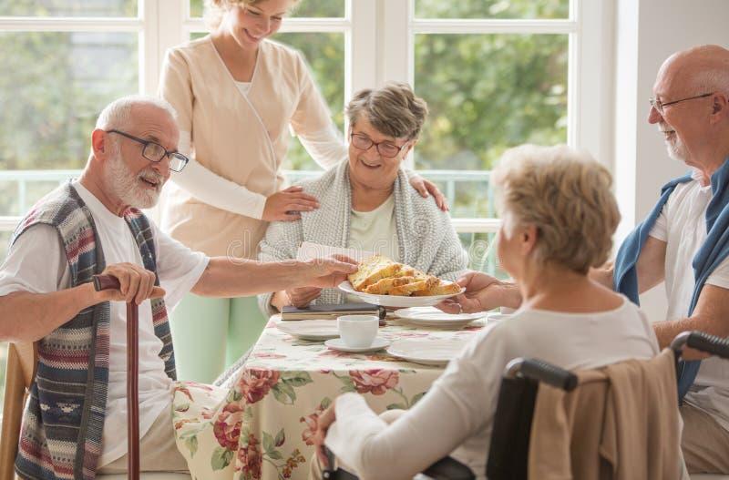 Grupo de amigos com a equipe de tratamento útil que senta-se junto na tabela na sala de jantar do lar de idosos e que come o bolo imagem de stock
