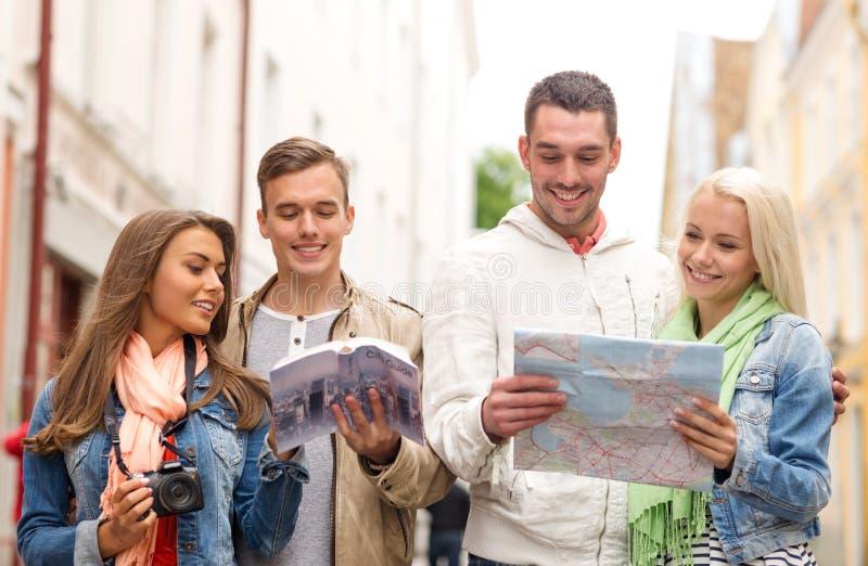Grupo de amigos com guia, mapa e câmera da cidade fotos de stock royalty free