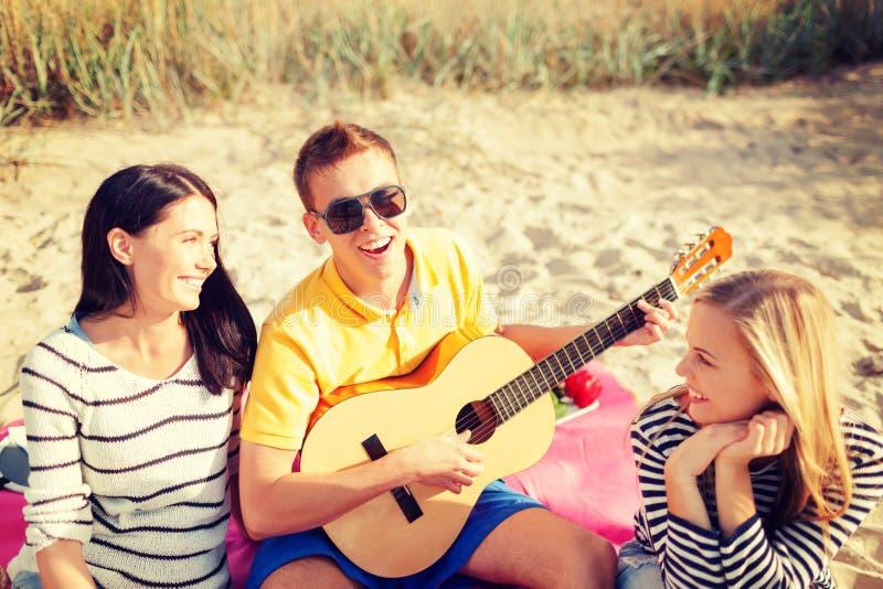 Grupo de amigos com a guitarra que tem o divertimento na praia fotografia de stock royalty free