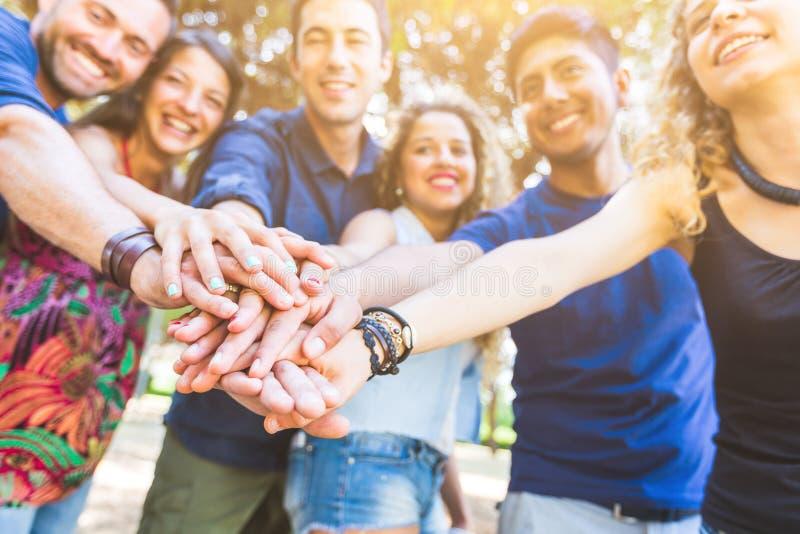 Grupo de amigos com mãos na pilha fotos de stock royalty free