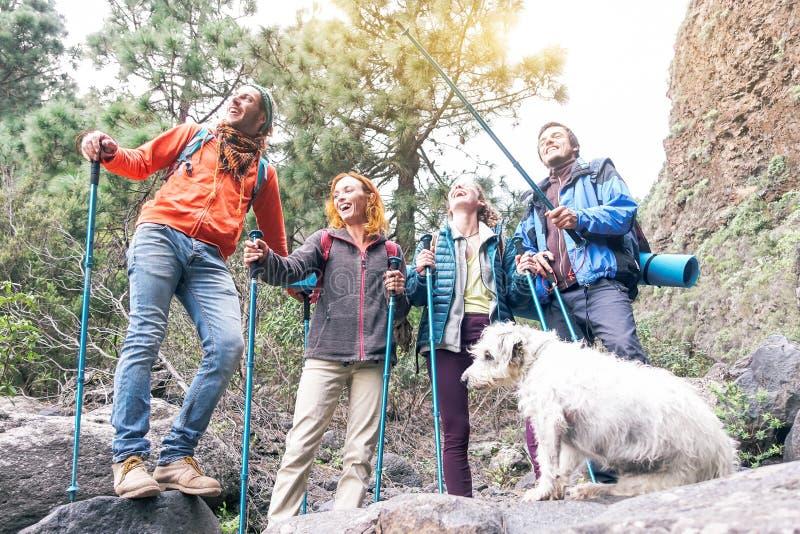 Grupo de amigos com mochilas fazendo trekking excursion na montanha com seus animais de estimação - Jovens turistas caminhando imagens de stock