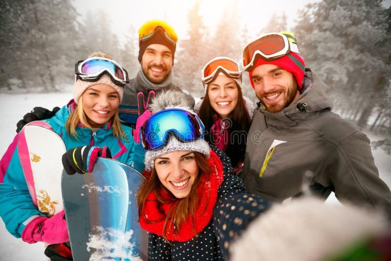 Grupo de amigos com o esqui em feriados de inverno - esquiadores que têm o divertimento fotos de stock royalty free
