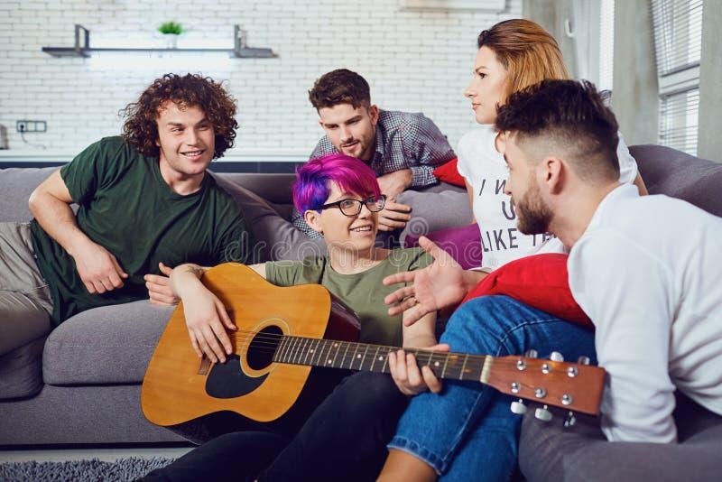 Grupo de amigos com uma guitarra em um partido em uma sala imagens de stock royalty free