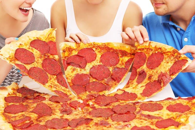 Grupo de amigos con la pizza fotografía de archivo
