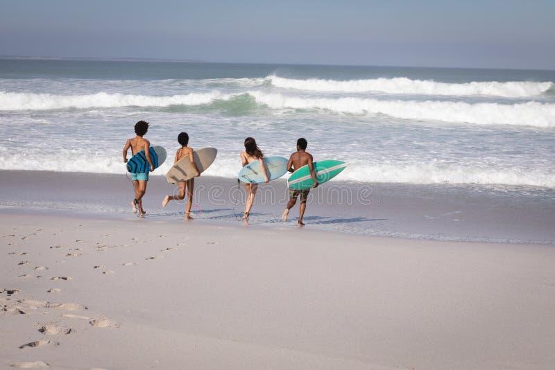Grupo de amigos con la tabla hawaiana que corre hacia el mar en la playa en la sol foto de archivo libre de regalías