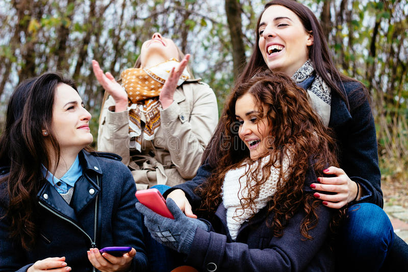 Grupo de amigos con un smartphone imagen de archivo