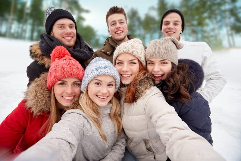 Grupo de amigos de sorriso que tomam o selfie fora imagem de stock
