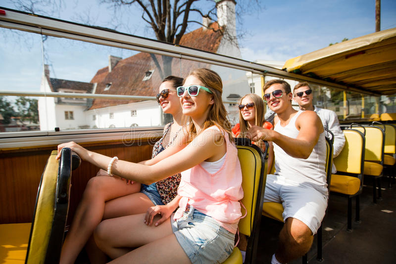 Grupo de amigos de sorriso que viajam pelo ônibus de excursão fotografia de stock
