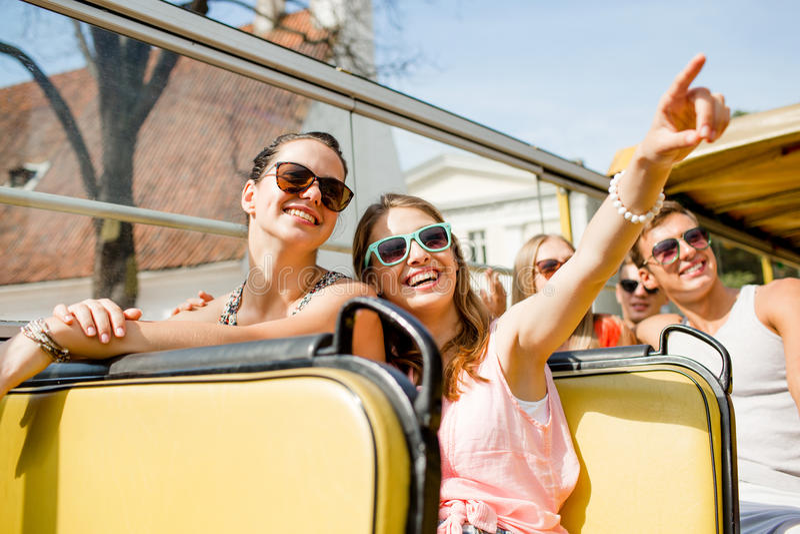 Grupo de amigos de sorriso que viajam pelo ônibus de excursão fotos de stock