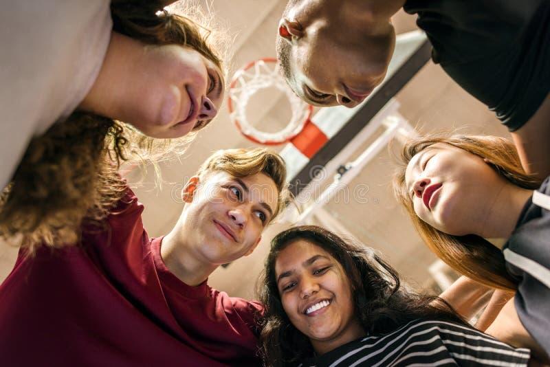 Grupo de amigos del adolescente en un concepto del trabajo en equipo y de la unidad de la cancha de básquet fotografía de archivo