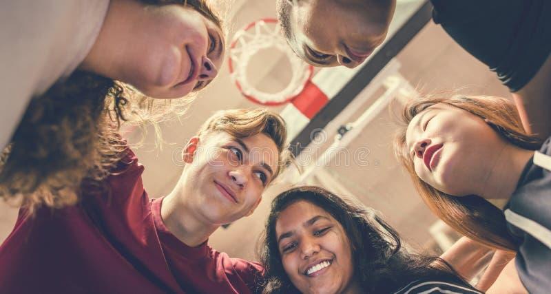 Grupo de amigos del adolescente en un trabajo en equipo y un tog de la cancha de básquet imagen de archivo libre de regalías
