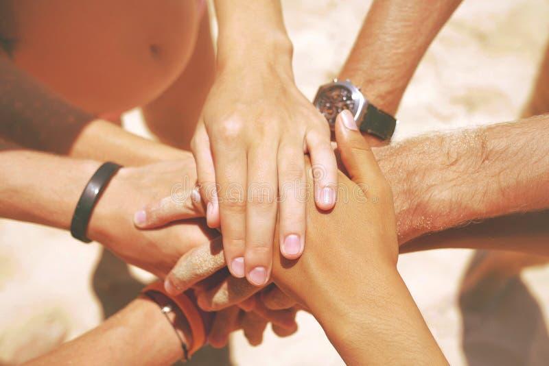 Grupo de amigos del inconformista de la raza mixta en la playa con sus manos apiladas Brazos de la gente joven con en la pila lif imagen de archivo