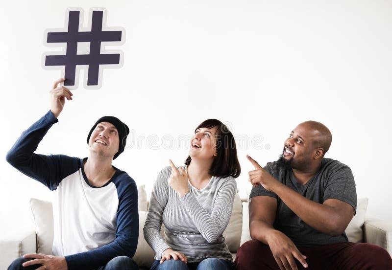 Grupo de amigos diversos que sentam-se no sofá que guarda um ícone do hashtag imagem de stock