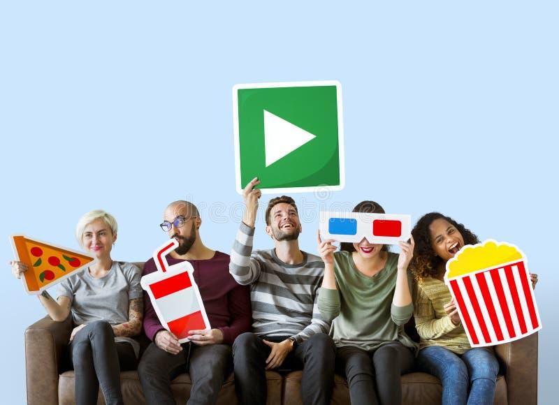 Grupo de amigos diversos que sostienen emoticons de la película foto de archivo