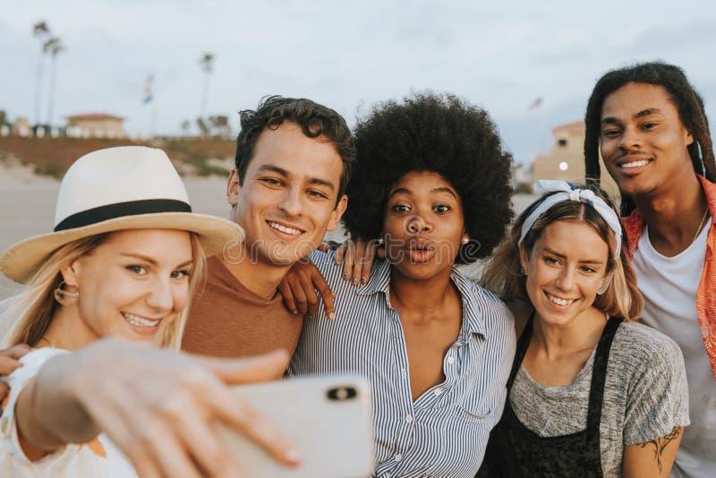 Grupo de amigos diversos que tomam um selfie na praia fotografia de stock