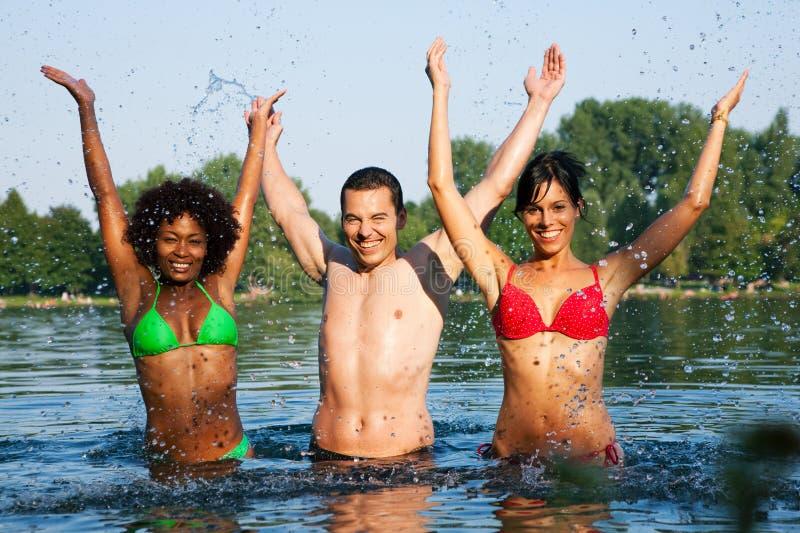 Grupo de amigos - divertimento no lago imagens de stock