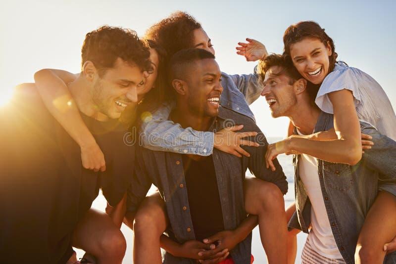 Grupo de amigos el las vacaciones que tienen raza del transporte por ferrocarril en la playa foto de archivo