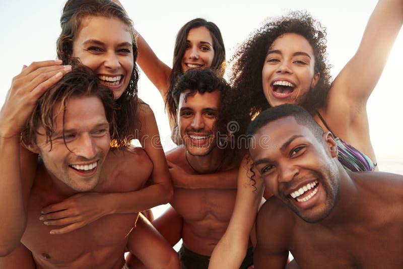 Grupo de amigos el las vacaciones que tienen raza del transporte por ferrocarril en la playa imagen de archivo libre de regalías